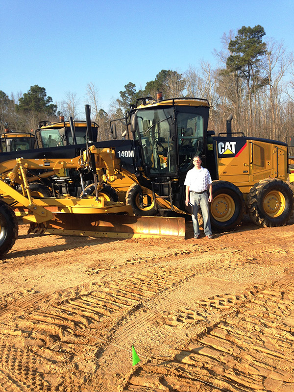 Scott Smith Standing in front of grader